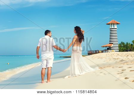 Beautiful young pregnant couple on the Caribbean coast. Happy pregnancy poster