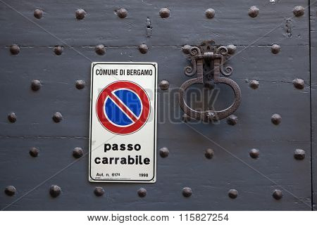 BERGAMO, ITALY - NOVEMBER 4, 2015: Old metal doorknocker and the No Parking sign on the black painted wooden gate fixed with rivets in Bergamo, Lombardy, Italy.