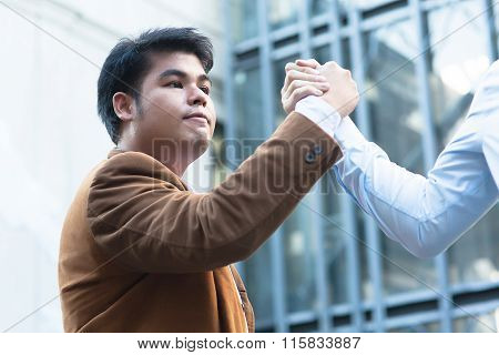 Asian Businessman Grasping Hands With His Trusted Colleague