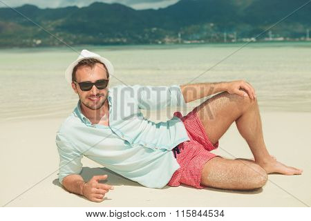 portrait of smiling hansome man lying on the beach while wearing shirt, pants, hat and sunglasses