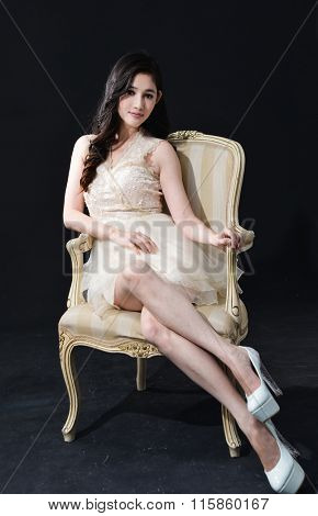 Portrait of fashion model in sexy clothes sitting old chair on black  background