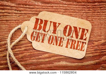 buy one get one free sale sign - a paper price tag against rustic red painted barn wood - shopping concept