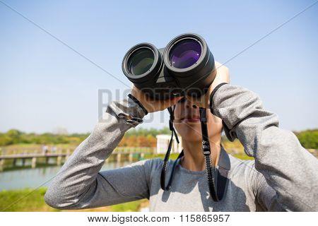 Woman looking though binocular for bird watching
