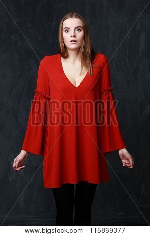 Young embarrassed woman in red dress on gray background poster