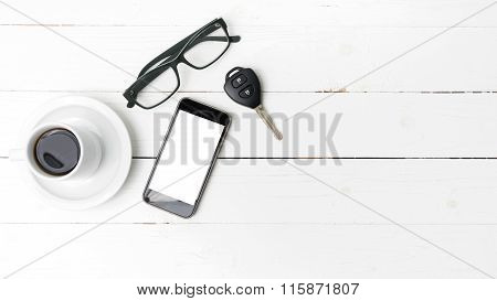 coffee cup with phone eyeglasses and car key on white wood table