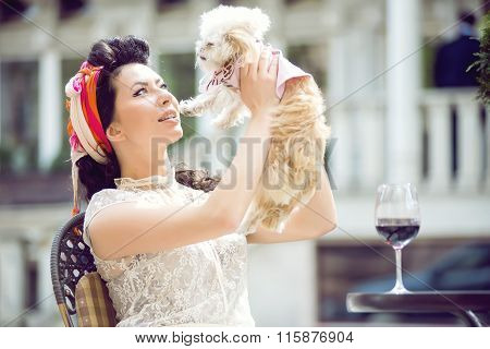 Young Italian woman with little puppy, drinking red wine in an outdoor cafe