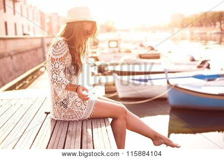 Young woman in hat and cute summer dress standing on the pier with peaceful town scenery, looking at