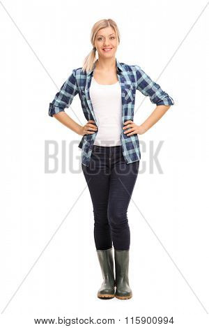 Full length portrait of a young woman in blue checkered shirt and green rubber boots isolated on white background
