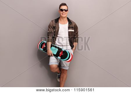 Young male skater holding a skateboard and leaning against a gray wall