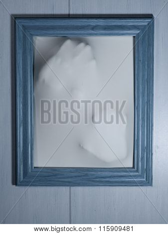 Creepy Bluetone Picture Frame With Something Coming Out Of It