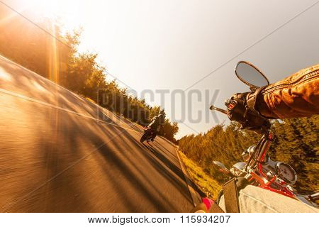 Man seat on the motorcycle on the forest road during sunrise.