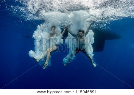 Underwater view of the young couple having fun and jumping into the clear sea from a boat