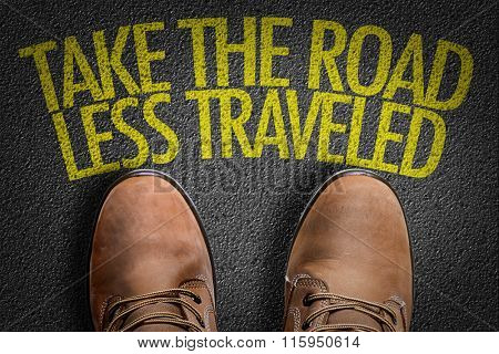 Top View of Boot on asphalt with the text: Take The Road Less Traveled