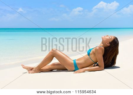 Suntan bikini woman relaxing on beach vacation sunbathing/sun tanning on perfect white sand turquoise beach for summer holidays. Asian model with sexy body and blue swimwear for weight loss concept.