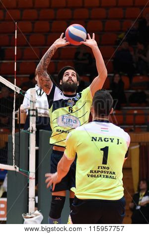 KAPOSVAR, HUNGARY - JANUARY 16: Balint Magyar posts the ball at a Hungarian National Championship volleyball game Kaposvar (green) vs. Sumeg (blue), January 16, 2016 in Kaposvar, Hungary.