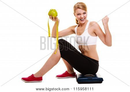 Woman sitting on weighing scale holding grapefruit and measurement tape raises raising her arms. Successful diet dieting slimming. Healthy lifestyle and body care concept. poster
