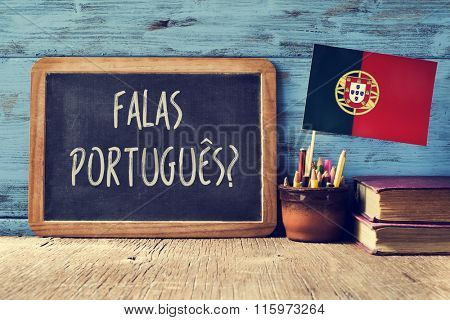 a chalkboard with the question question falas portuges? do you speak Portuguese? written in Portugese, a pot with pencils, some books and the flag of Portugal, on a wooden desk