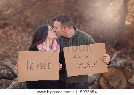 engaged couple kissing and holding cardboard signs