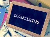 Handwritten Downsizing on a Chalkboard. Composition with Chalkboard and Ring Binders, Office Supplies, Reports on Blurred Background. Toned Image. poster