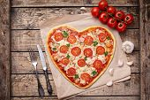 Vegetarian heart shaped pizza margherita with tomatoes, mozzarella, parsley and garlic on vintage wooden table background. Food concept of romantic love. Rustic style and natural light. poster