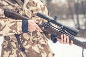 Close up and details of a man wearing a camouflage suit holding a sniper rifle or gun poster