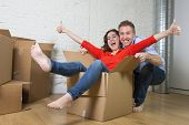 young happy American couple unpacking having fun enjoying together moving in a new house or flat playing with woman or wife inside cardboard box and husband or boyfriend pushing in real estate concept poster