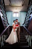 Bride And Groom Standing At Ladder Indoor Of Old Building