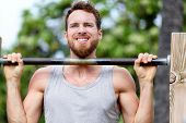 Crossfit fitness man exercising chin-ups workout. Young male adult trainer athlete portrait closeup with hands holding on monkey bars at outdoor gym doing a chin-up strength training muscle exercise. poster
