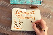 Retro effect and toned image of a woman hand writing a note with a fountain pen on a notebook. Handwritten text RP RETIREMENT PLANNING business success concept poster