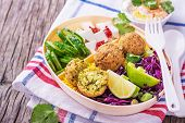 Box Lunch on the road for a picnic or to the office for lunch with cous cous, falafel chick peas, red cabbage salad, slices of cucumber, feta cheese and salad hummus in a white plastic container with a fork and spoon decorated with sprigs of cilantro. sel poster