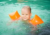 Baby with armbands in swimming pool poster