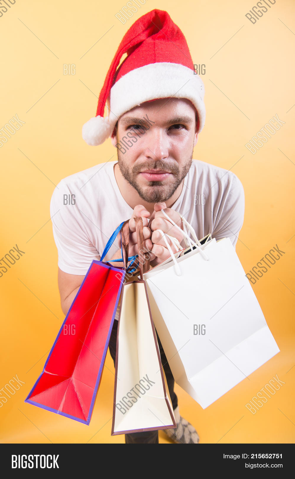 0d2cc6b58e7a7 Man shopper in santa hat with paperbags. New year xmas presents. Macho hold  shopping bags on orange background. Winter holidays celebration. Black  friday ...