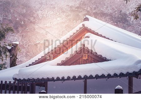 Close up roof top of wooden house or cottage covered with white snow after strong snow falling at countryside.