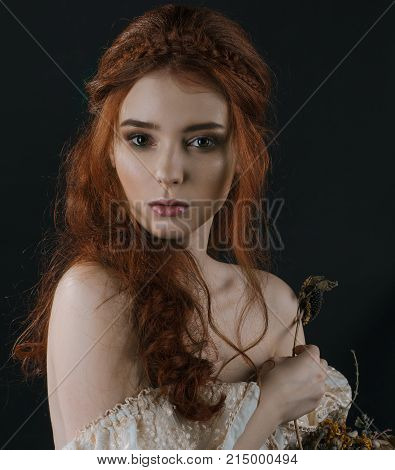 A close-up portrait of a red-haired young woman in a vintage gold dress with bare shoulders with a dry bouquet in hands on a black background. A princess. Fairy tale. Art photo