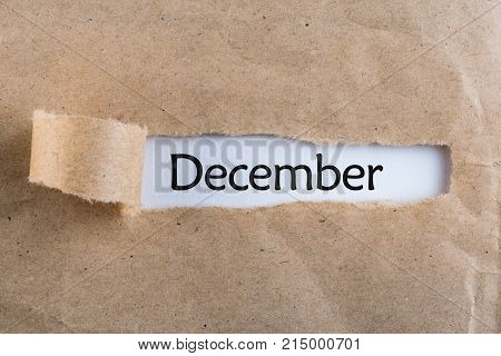 December - message appearing behind ripped brown paper. Winter, christmas and new year time.