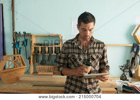 Young joiner drinking coffee and reading e-mails from clients on tablet computer