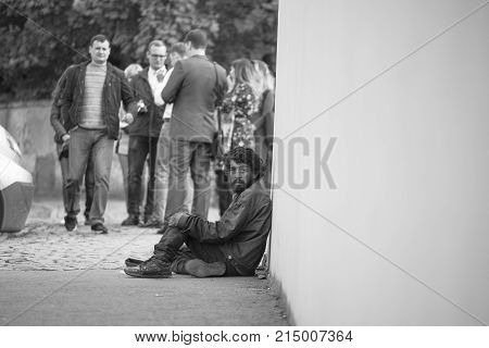 Uzhgorod Ukraine - 14.10.2017. Beggar man on the background of a white wall asks for help. Black and white photo.