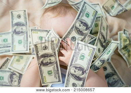 Cute baby boy playing with money, closed his eyes with hands to be invisible or not willing to see, playing fun peek a boo.
