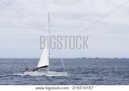 NORTH SEA, NORWAY ON JULY 04. View of a Swedish sailboat in tailwind on July 04, 2010 in North Sea, Norway. Islands in the background, unidentified people. Editorial use.