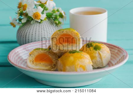 Delicious Chinese pastry or moon cake filled with mung bean paste and salted egg yolk on ceramic plate served with tea on lite blue wood table in side view. Homemade Chinese pastry for tea time. Moon cake or Chinese pastry ready to served.