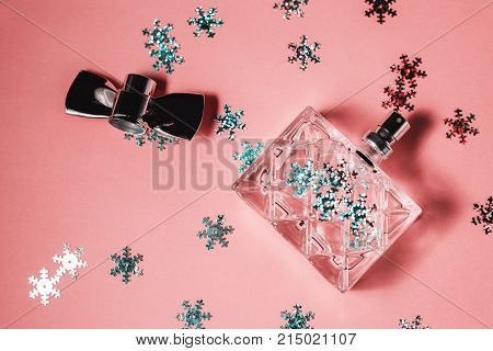 Female perfume with cristmass decoration on pink background