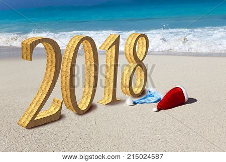 Happy new year card. Two New Year's caps of Santa Claus on beach and inscription 2018 in the sand