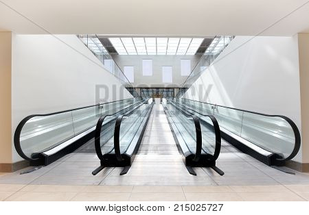 Two empty escalators one ascending and one descending side by side in a brightly lit commercial building