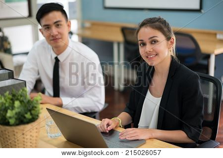 Portrait of smiling business woman with coworkers at office.