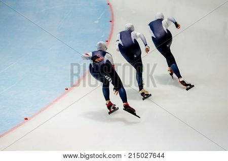 back women athletes speed skaters in warm up turn