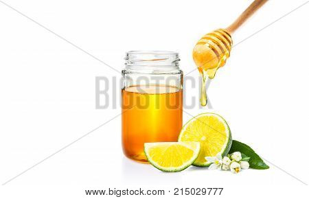 honey dipper with honey dripping down honey jar and cut fresh lime on isolated white background room for adding text or copy space