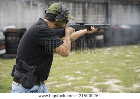 Man shooting shot gun on an outdoor shooting range selective focus