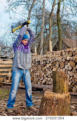A man a woodcutter with a yellow ax chop wood for a fire on the background of a pile of firewood.