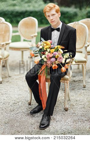 The bridegroom is waiting for the bride with the flowers