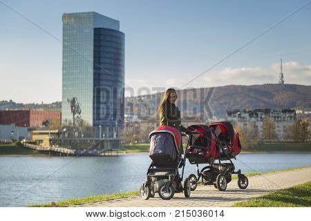 A beautiful mother is sleeping her three kids in her strollers on a walk by the lake